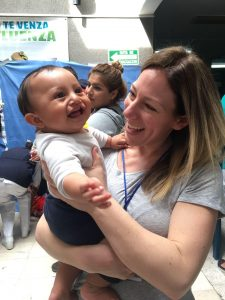 Melissa white holds a smiling baby on a medical mission volunteer trip.
