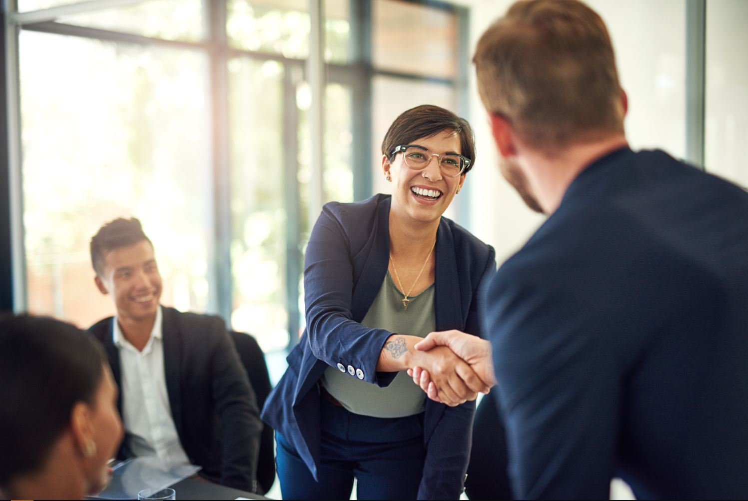 Business woman shaking hands with a man at a meeting.