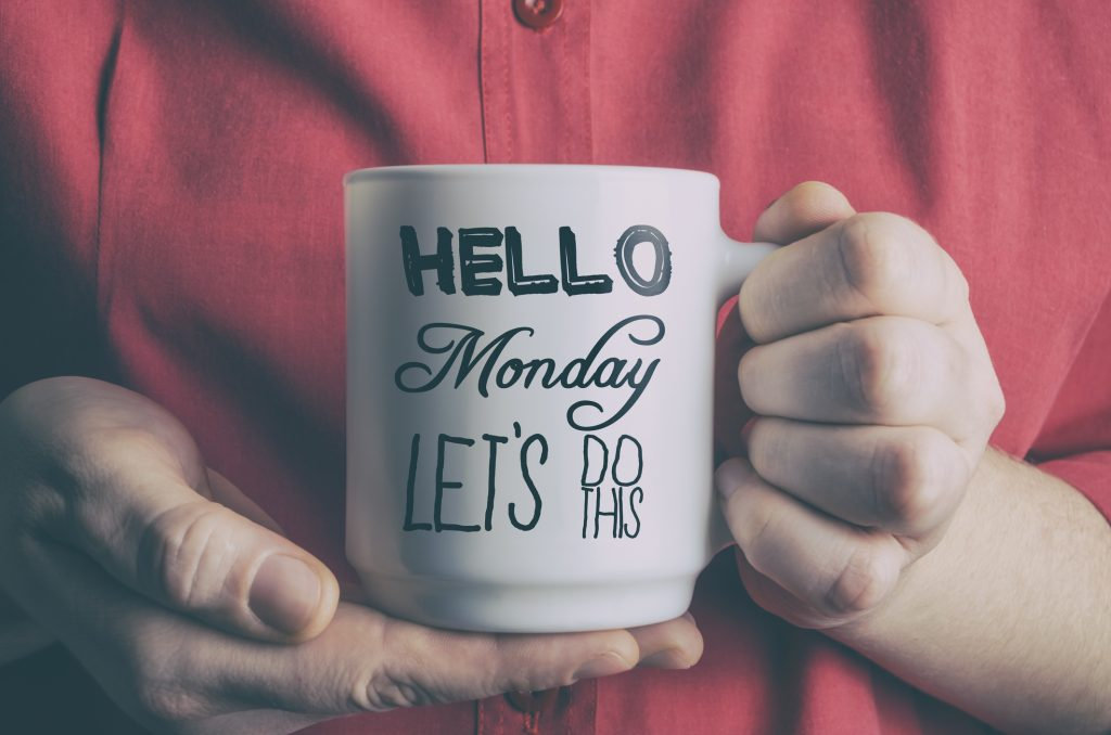 "Image of a person holding a cup in his/her hands that says ""Hello Monday Let's Do This!"""