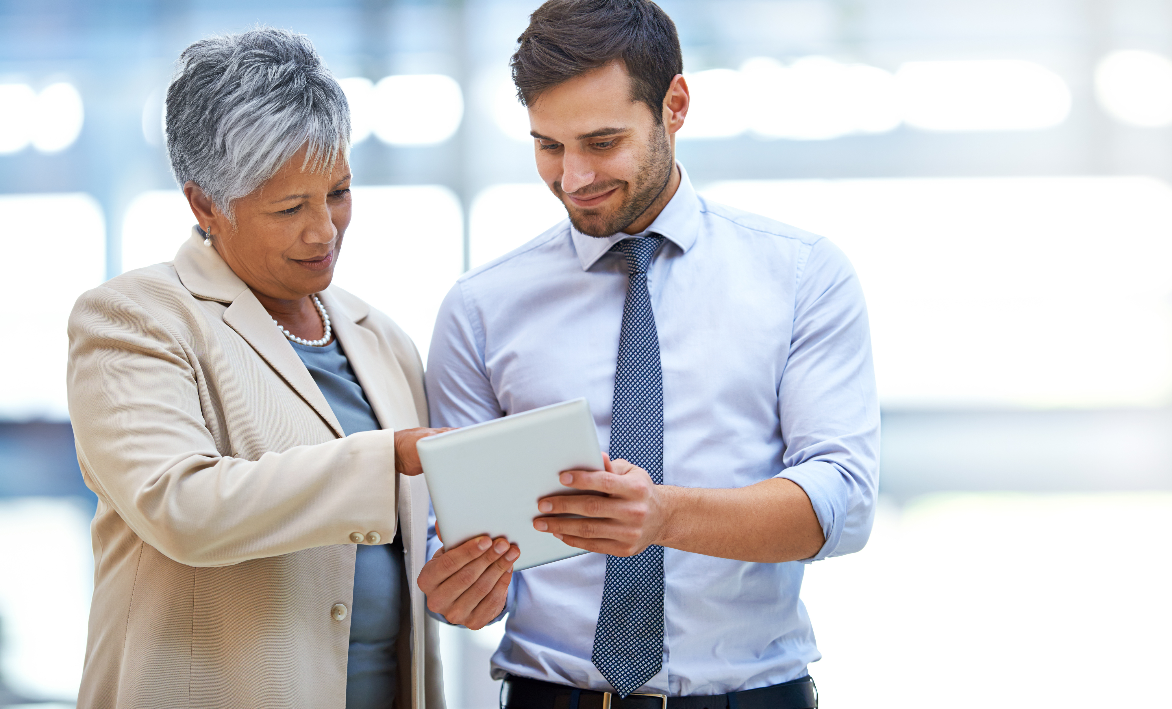 Two business people discussing a transaction using a tablet.