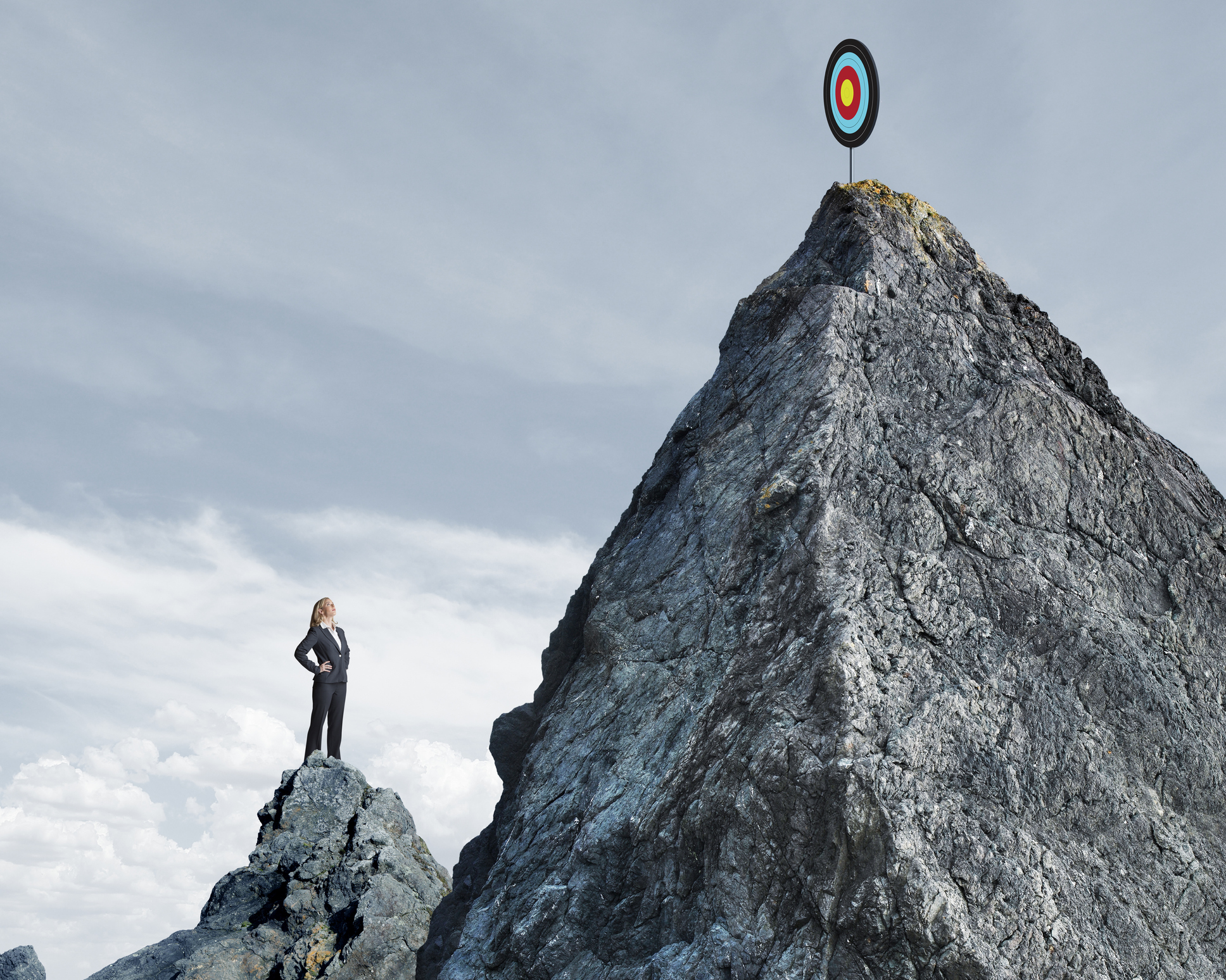 A businesswoman stands on top of a small mountain and looks up at a target that sits on top of a taller mountain top that rises in front of her.