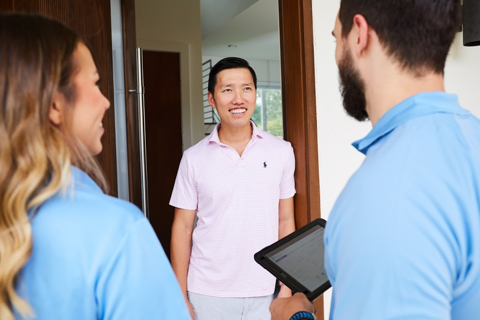 Door to door residential sales reps pitch a customer at the door to their house.