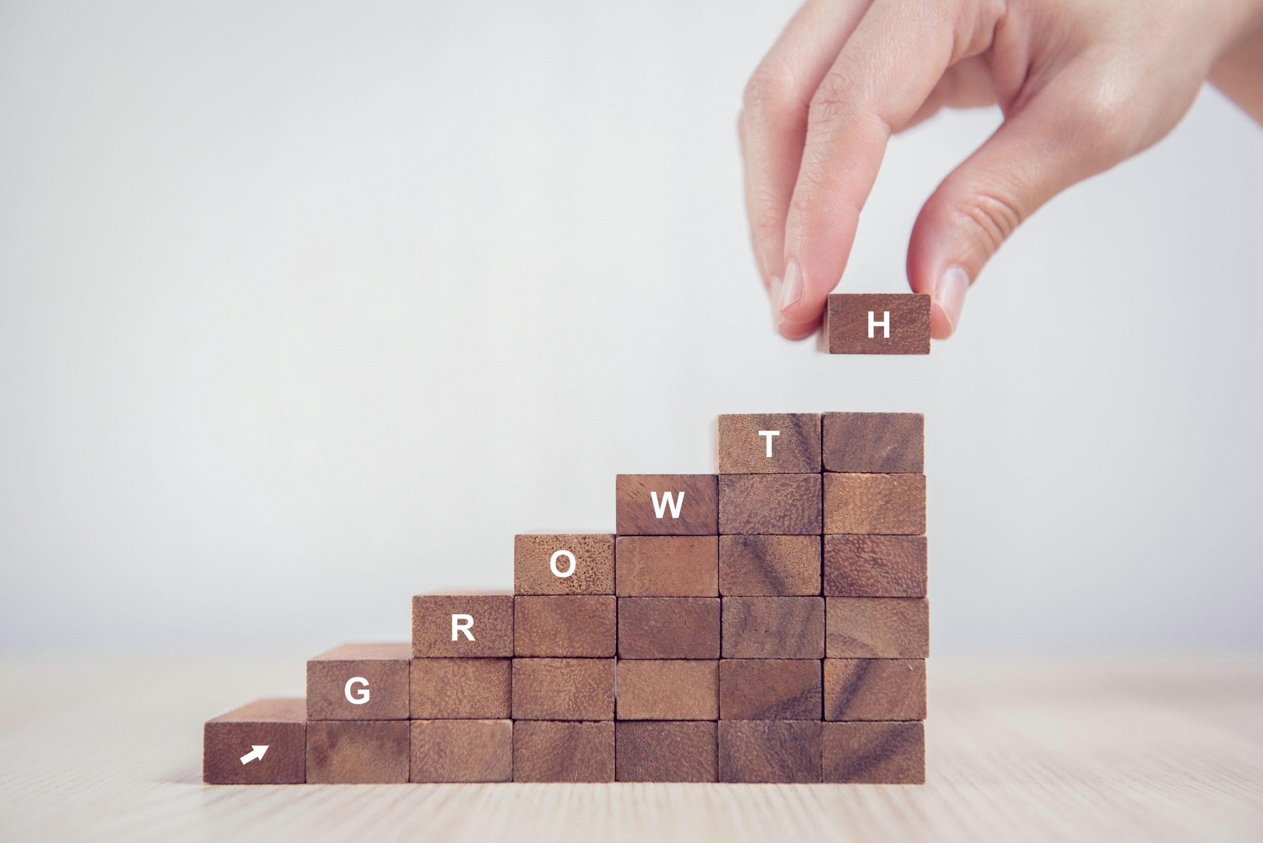 How to scale your sales program. Blocks stacked up spelling out growth.