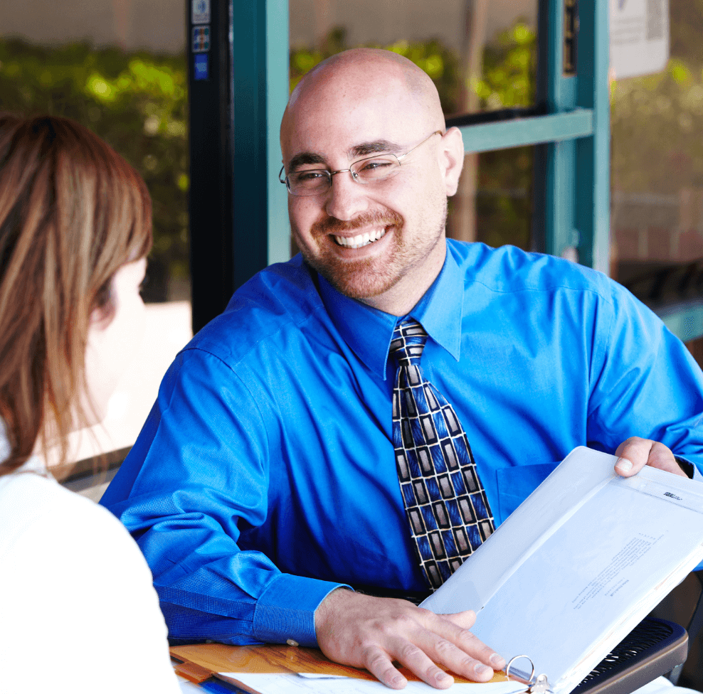 Image of a sales rep sitting outside, making a presentation to a customer.