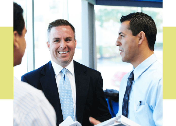 Image of a sales rep meeting with two businessmen.
