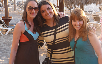 Jessica Pope poses with two female Cydcor colleagues on the beach.