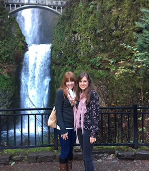 Jessica Pope poses with a friend in front of a waterfall.