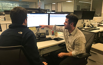 Patrick Geraghty shows a colleague how to do something in Salesforce