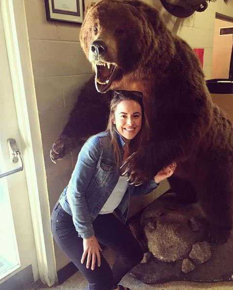 Vanessa Gonzalez poses with a giant bear while on a trip.