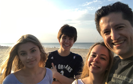 Matt Yarahmadi poses with his family on a beach.